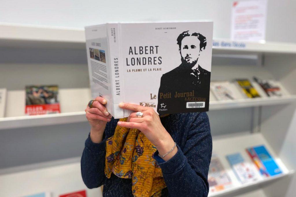usager consultant un ouvrage dans la bibliothèque