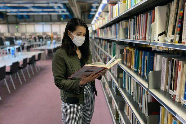usager avec un masque dans les rayonnages de la bibliothèque
