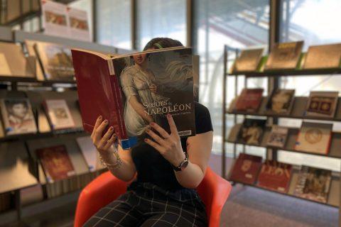 usager consultant un ouvrage dans le salon Arts et Littérature de la bibliothèque.