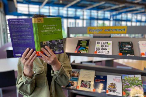usager consultant un ouvrage sur un meuble de valorisation.