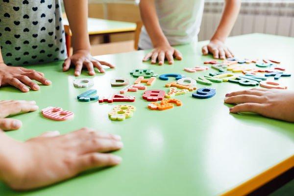 mains d'enfants déplaçant des lettres sur une table