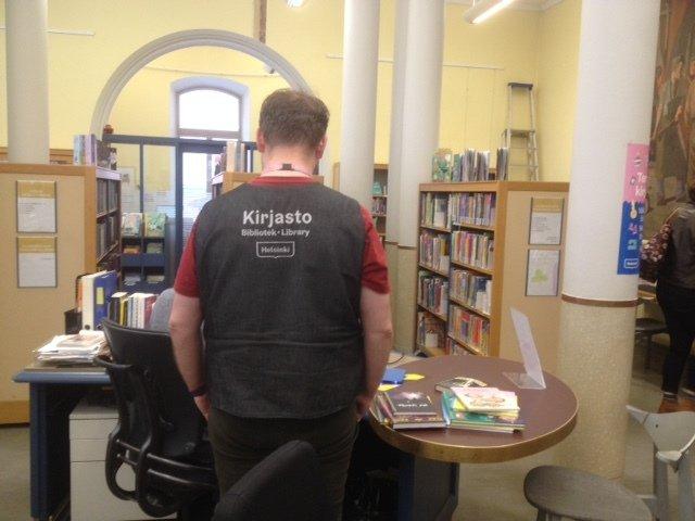 bibliothécaire de dos avec gilet signalant sa fonction