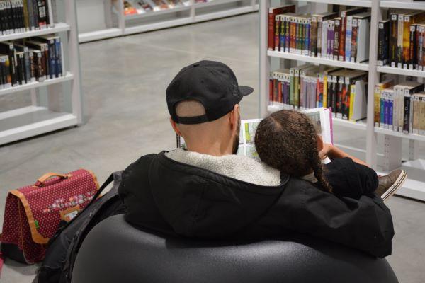 Photographie représentant un père et sa fille dans la bibliothèque Assia Djebar