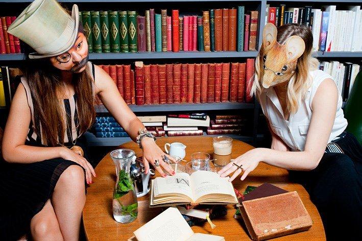 Photographie de deux femmes masquées lisant un même livre devant une bibliothèque