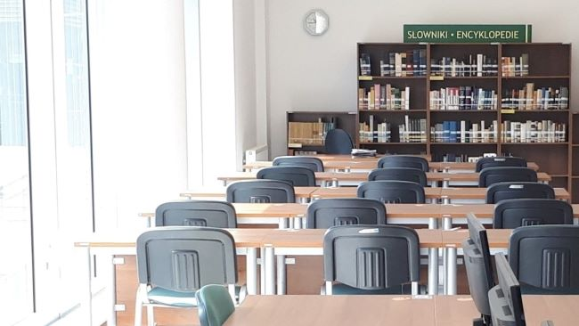 Photographie d'une salle de la bibliothèque vide avec tables et chaises