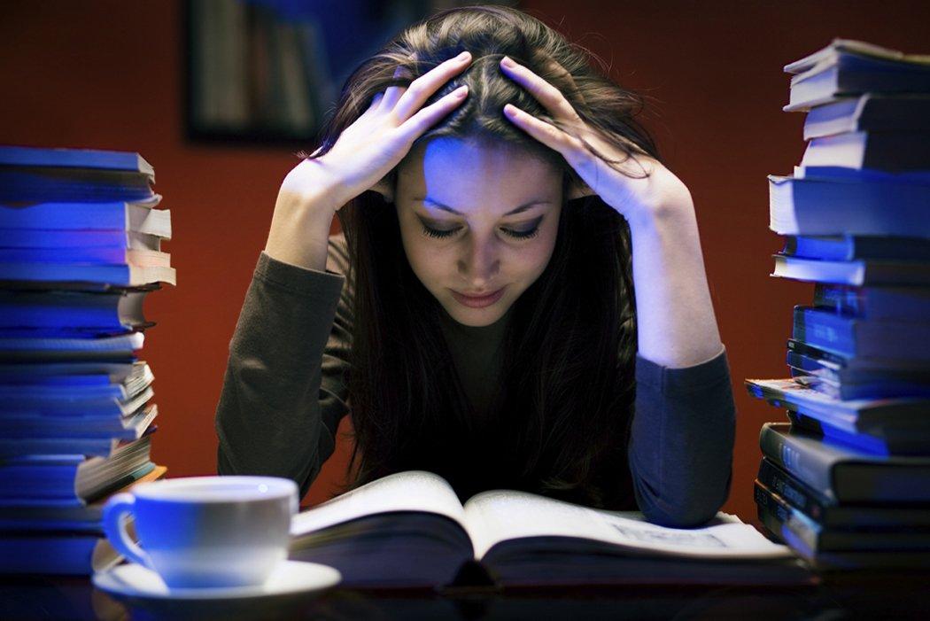 photo d'une jeune femme en train de lire qui se tient la tête