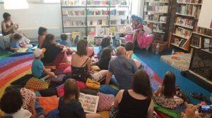 Photographie du public écoutant une lecture par un drag queen dans la bibliothèque