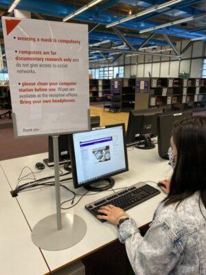 Photographie d'un usager portant un masque devant le panneau de consignes sanitaires rédigées en anglais
