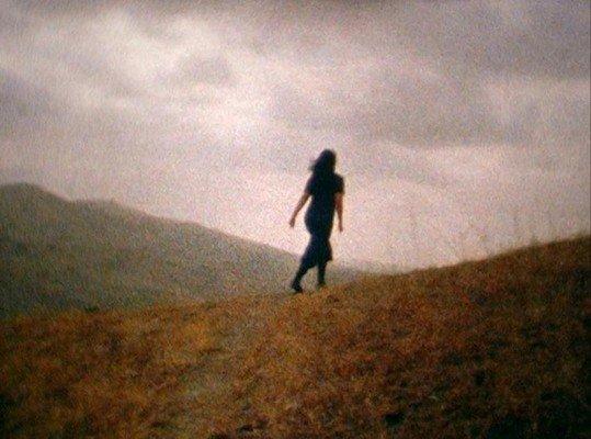 Pgotographie d'une jeune femme de dos courant sur une colline