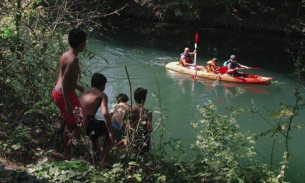 photographie du documentaire : enfants regardant une pirogue passant sur la rivière