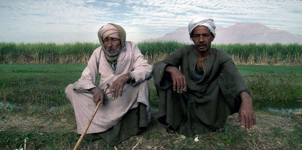Photographie de deux hommes assis assis et enturbannés au bord d'une route