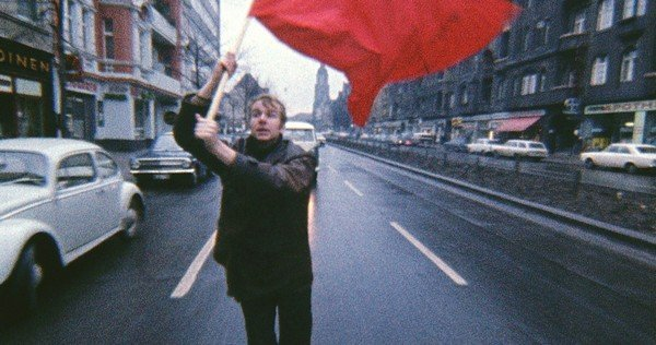 Photographie d'un jeune homme brandissant un drapeau rouge dans ka rue