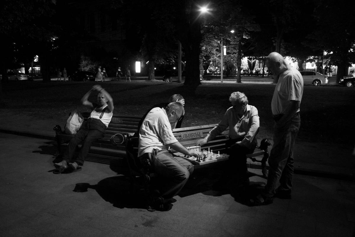 Photo de joueurs d'échecs sur un banc de nuit