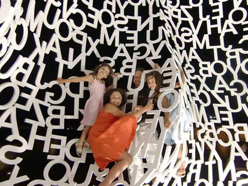 Photographie de trois filles et leur père sur trame de lettres