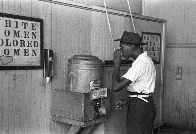 Photo d'un Noir devant une fontaine