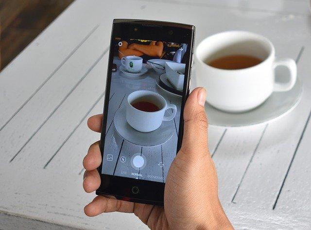 smartphone devant une tasse de thé