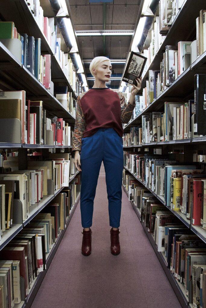 Elle prend la pose dans les rayonnages de livres