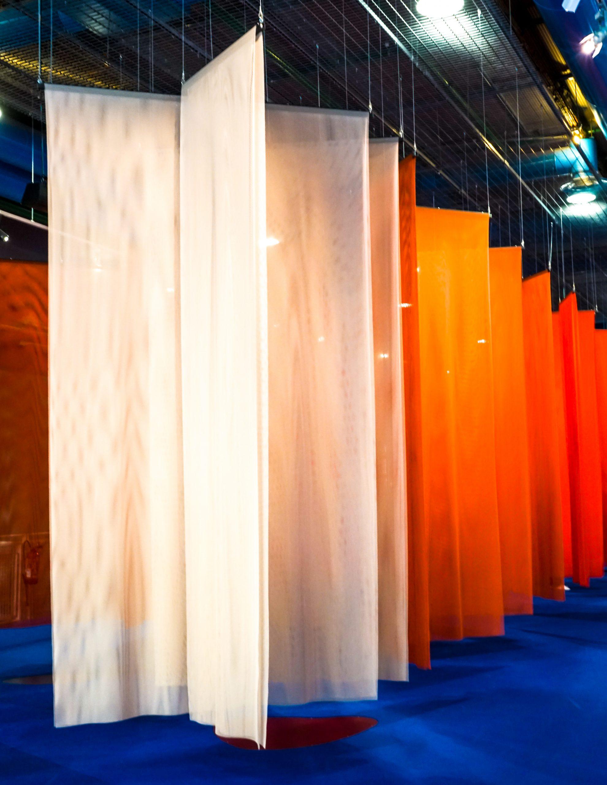 Des pans de tissus translucides aux couleurs chaudes pendent du plafond