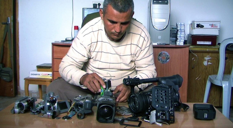 Emad Burnat devant ses cinq caméras brisées.
