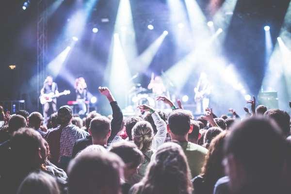 Scène de concert : un groupe de musiciens rock joue devant un public vu de dos