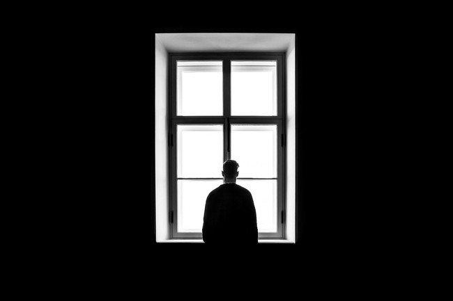 Un homme seul se tient immobile dans une pièce sombre. Debout, devant une haute fenêtre, il regarde à l'extérieur mais on ne devine rien à travers les vitres blanches.
