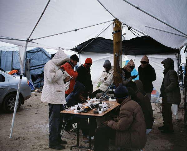 Migrants rechargeant leur téléphone sous une tente