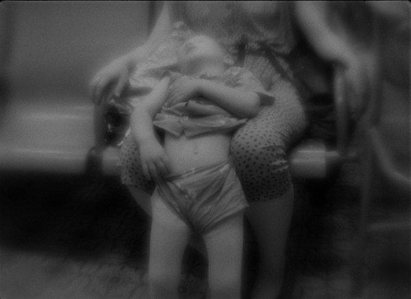 Un enfant dort sur les genoux de sa mère.