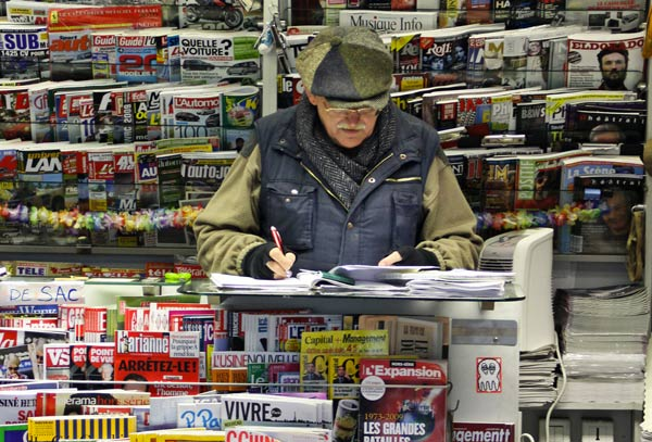 Kiosquier au milieu de journaux