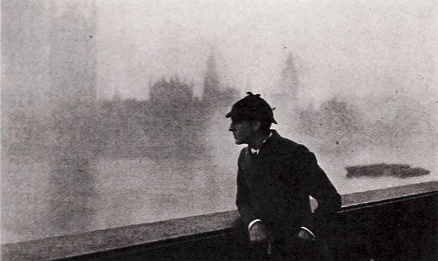 Photo en noir et blanc montrant un homme vétu comme Sherlock Holmes, accoudé à une balustrade au bord de la Tamise.