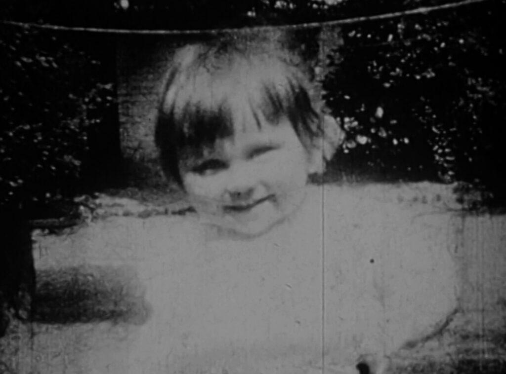 Une jeune enfant sur une image en noir et blanc,rayée.